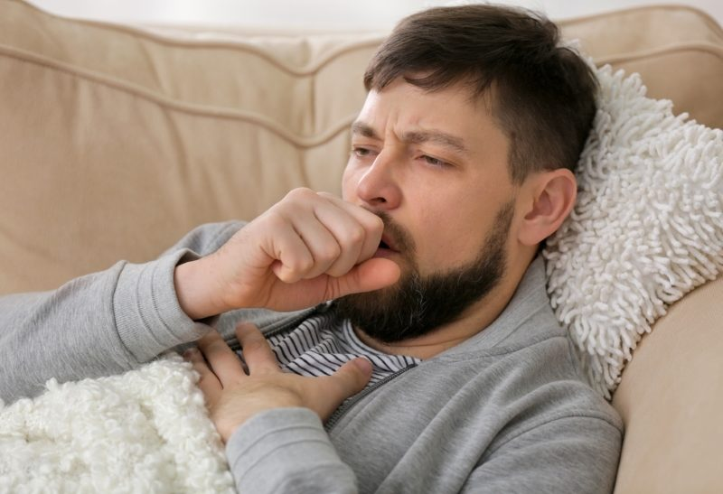 young-ill-man-lying-on-sofa-at-home
