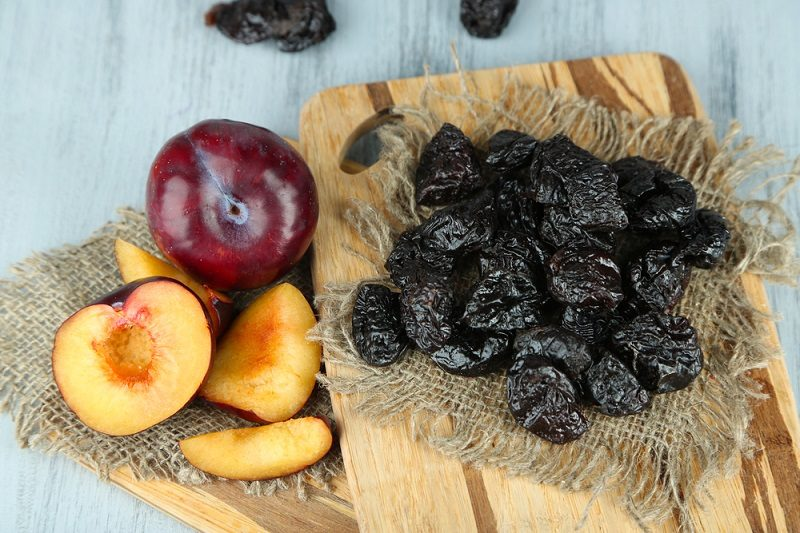 fresh-and-dried-plums-on-napkin-on-wooden-background