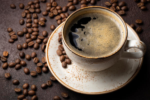 close-up-of-a-cup-of-black-coffee-and-coffee-beans-on-a-dark-background