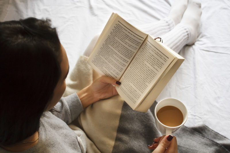 girl-reading-book-and-drinking-coffee-in-bed-in-the-morning